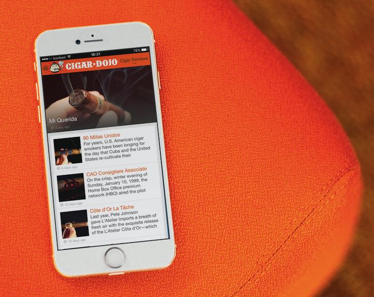 White iPhone 6 on a Orange Sofa running Cigar Dojo app