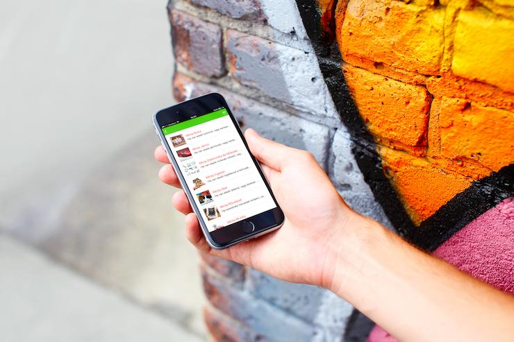 Female using Gazdagret app next to the graffiti wall